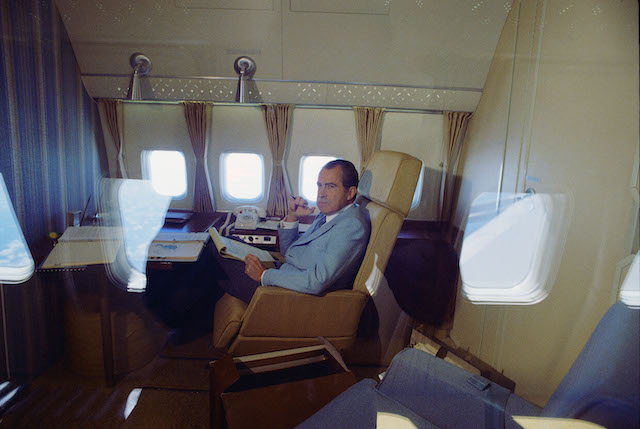 President Nixon studies his briefing materials on board Air Force One, enroute to China